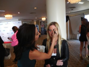 Makeup artist Maria Lee applies makeup to author and journalist Liz Crokin