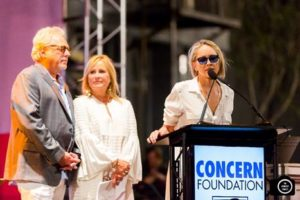 Sharon Stone speaking at the event as her sister, Kelly, and Bruce Singer receive their Spirit of Concern Humanitarians Award